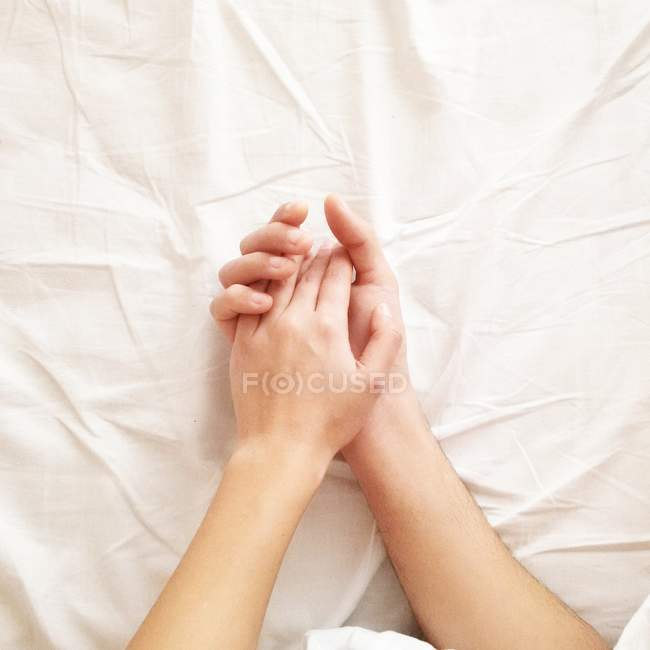 Couple lying in bed holding hands — Stock Photo