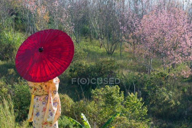 Femme portant kimono avec parapluie rouge — Photo de stock