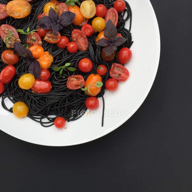 Black pasta with cherry — Stock Photo
