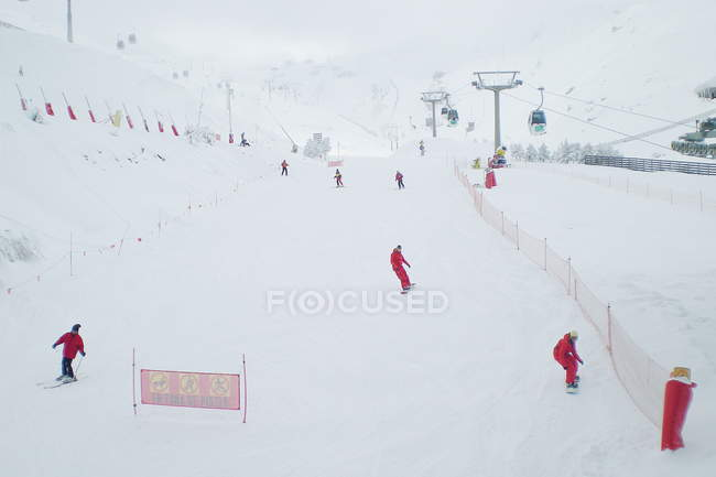 People skiing down ski slope — Stock Photo