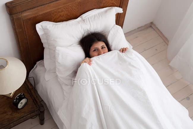 Teenage girl hiding under duvet — Fotografia de Stock