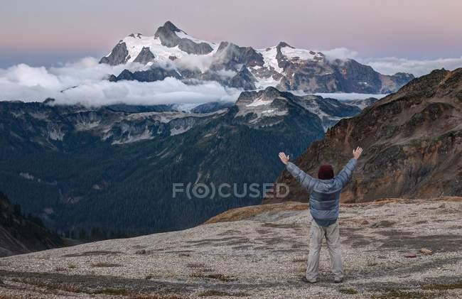 Человек стоит с поднятыми руками — стоковое фото