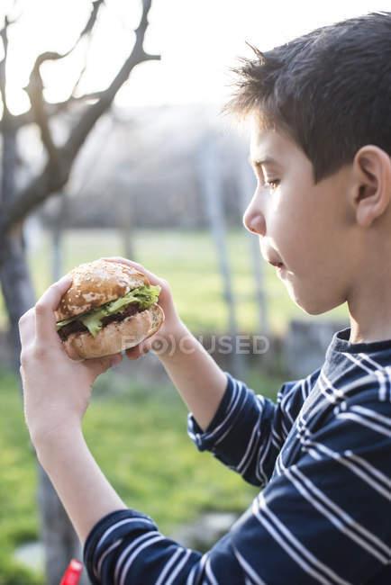 Niño sosteniendo hamburguesa en el jardín - foto de stock