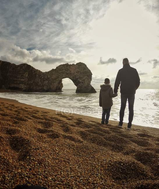 Father and son holding hands on beach — Stock Photo