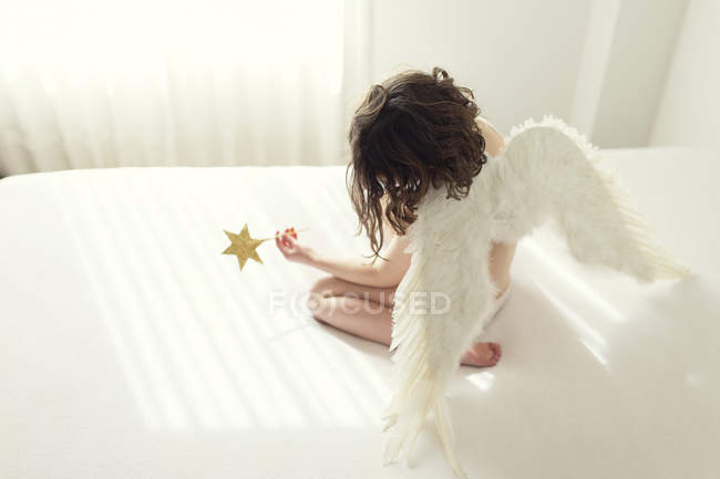 Girl sitting on bed dressed in angel wings — Stock Photo