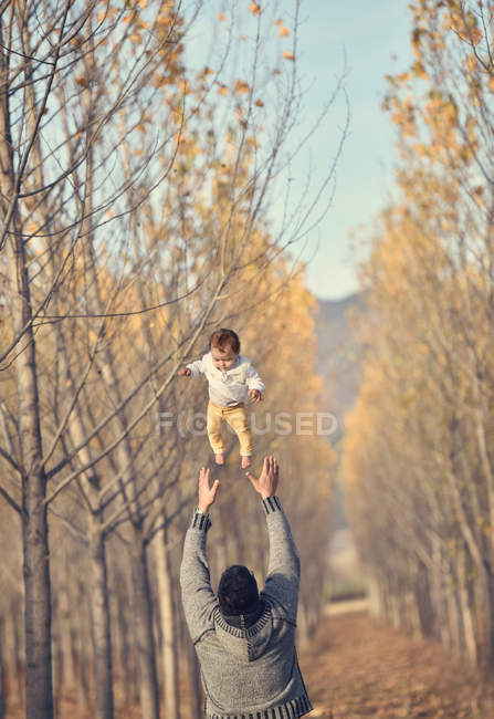 Man throwing baby girl in air — Stock Photo