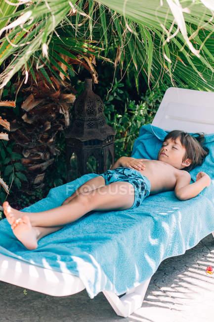 Мальчик спит на шезлонге — стоковое фото