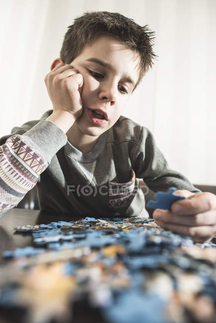 Boy assembling jigsaw puzzle — Stock Photo