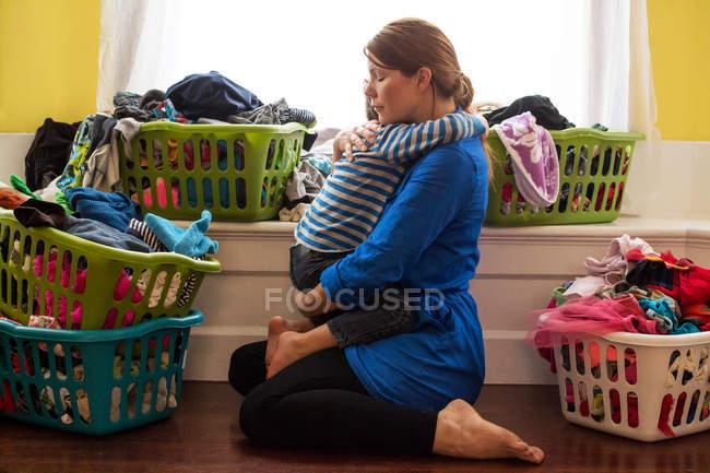 Мать с сыном, окруженный корзины прачечного — стоковое фото