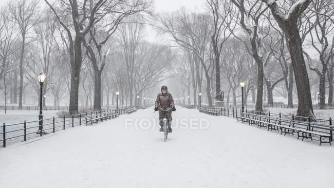 Женщина на велосипеде по снегу в Центральном парке — стоковое фото