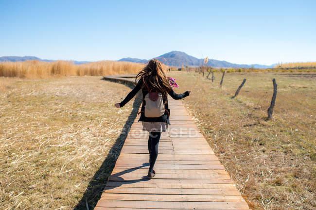 Женщина, идущая по деревянной дорожке — стоковое фото