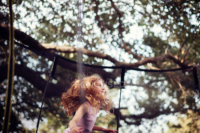 Girl jumping on trampoline — Stock Photo