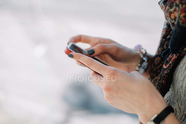 Female hands using mobile phone — Stock Photo