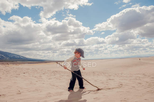 Boy writing in sand with stick — Stock Photo