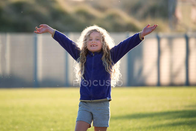 Girl standing with arms in air — Stock Photo