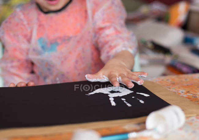 Boy making hand print with paint — Stock Photo