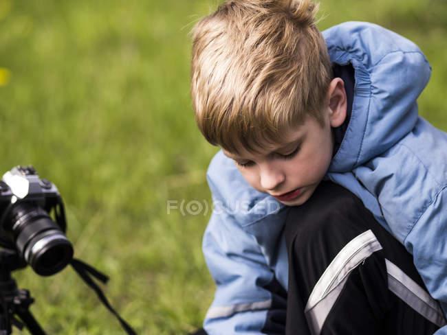 Мальчик с камерой на штативе фотографирует — стоковое фото