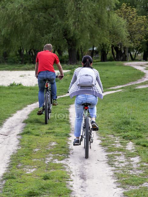 Família faz andar de bicicleta ao longo da estrada de terra — Fotografia de Stock
