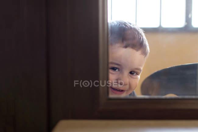 Хлопчик дивлячись через вікно — стокове фото