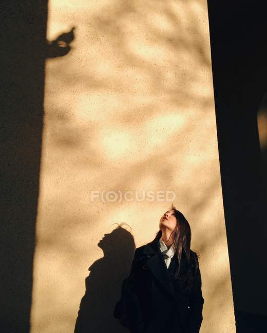 Woman standing against wall looking up — Stock Photo