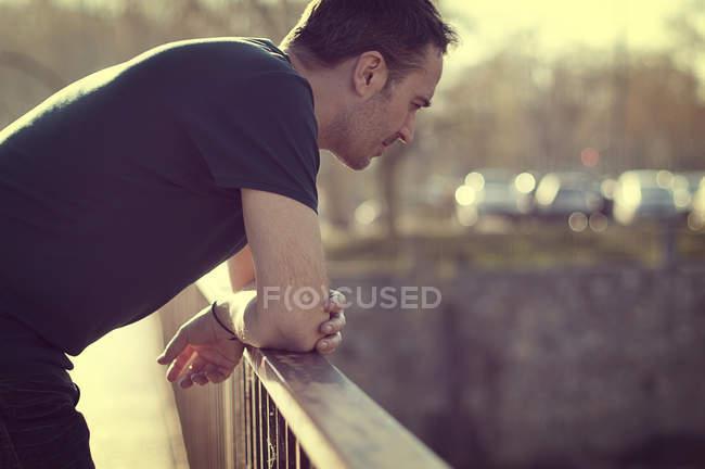Mann lehnt an Geländer — Stockfoto