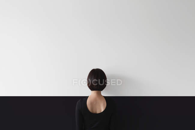 Woman standing facing wall — Stock Photo
