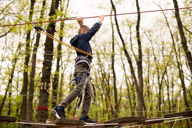 Boy in rope harness on climbing platform — Stock Photo