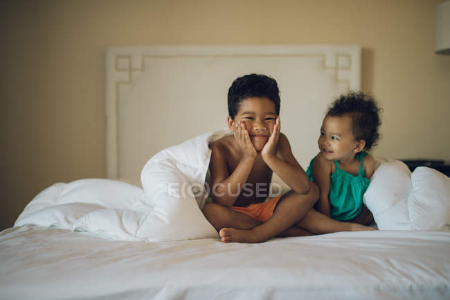 Petits enfants avoir du plaisir sur le lit — Photo de stock