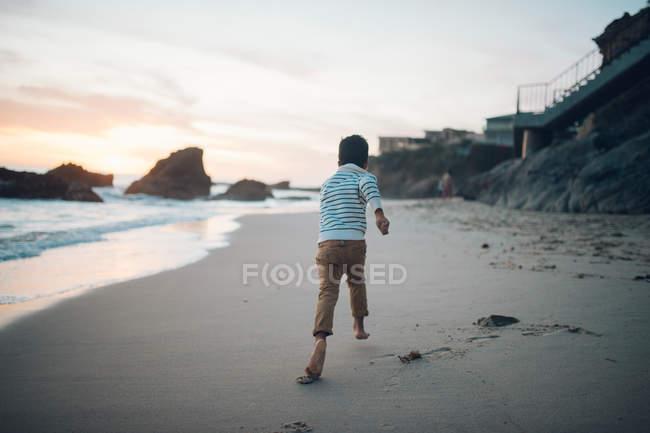 Junge läuft am Strand bei Sonnenuntergang — Stockfoto