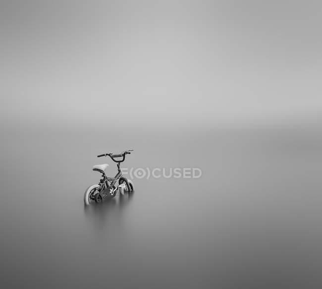 Fahrrad teilweise in grauen Hintergrund getaucht — Stockfoto