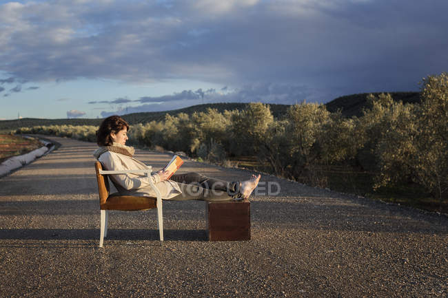 Woman sitting on chair and reading on road — Stock Photo