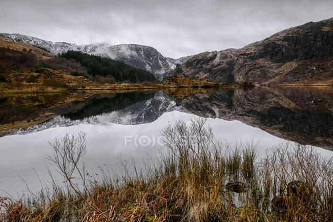 Montanhas, refletidas no lago — Fotografia de Stock