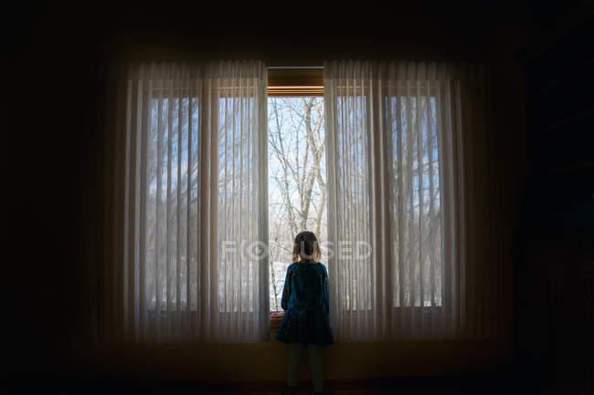 Дівчинка дивиться у вікно. — стокове фото