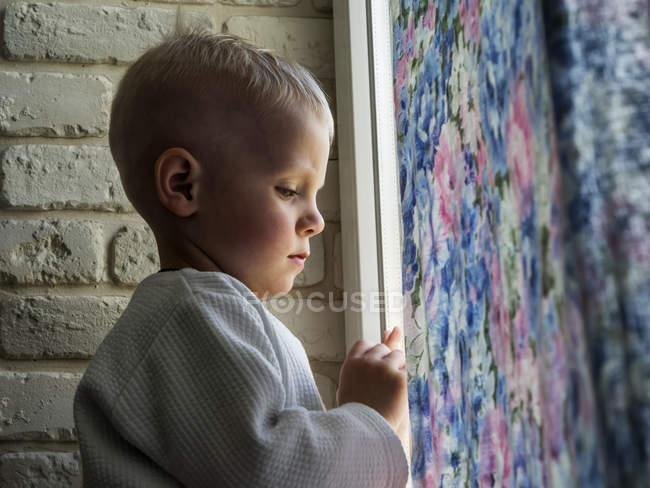 Мальчик смотрит в окно — стоковое фото