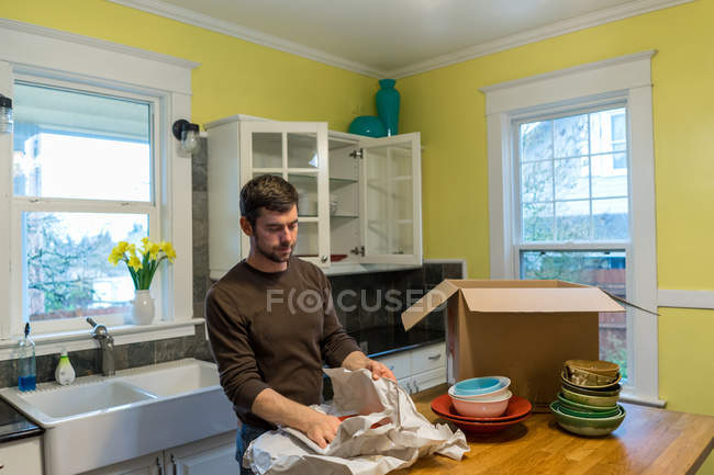Man packing up plates for house move — Stock Photo