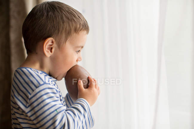 Хлопчик їсть шоколад пасхальне яйце — стокове фото
