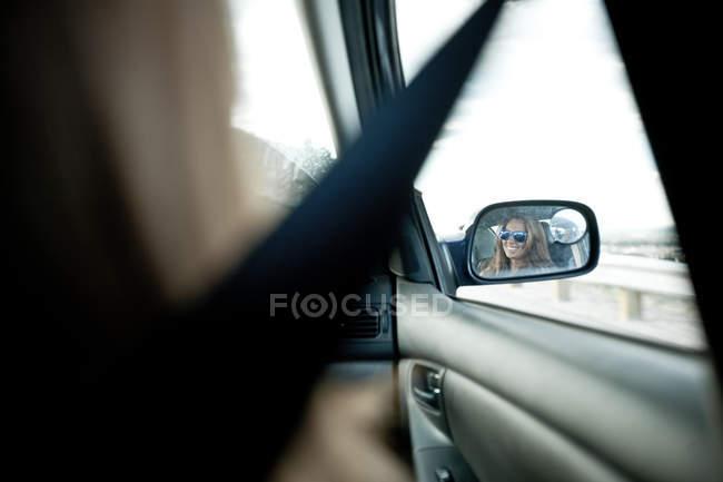 Frau im Außenspiegel des Autos — Stockfoto