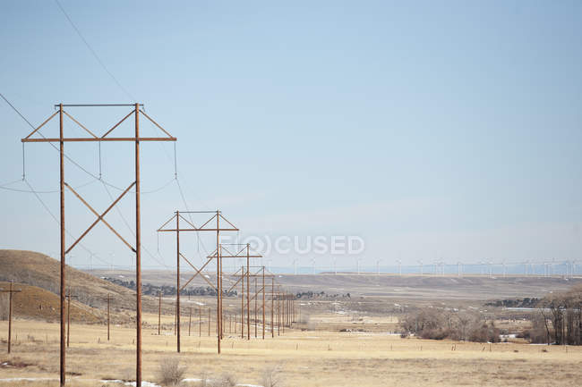 Power lines with wind farm in background — Stock Photo