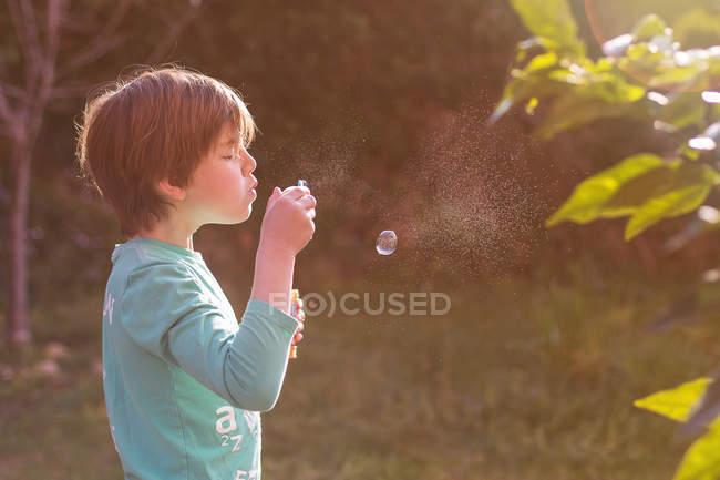 Мальчик пускает мыльные пузыри — стоковое фото