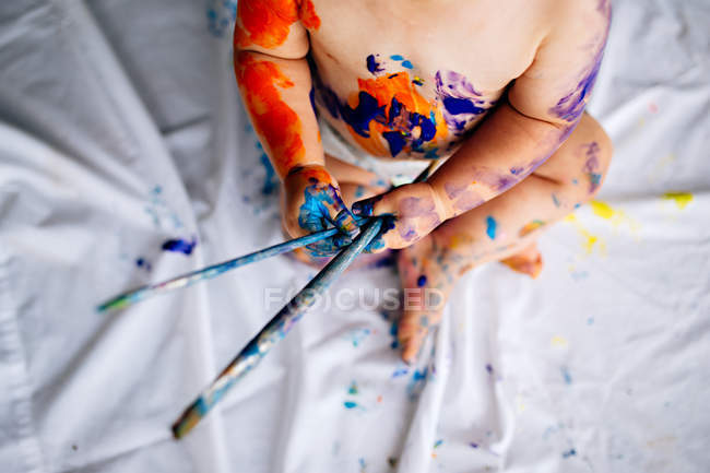 Baby boy covered in multi-colored paint — Stock Photo