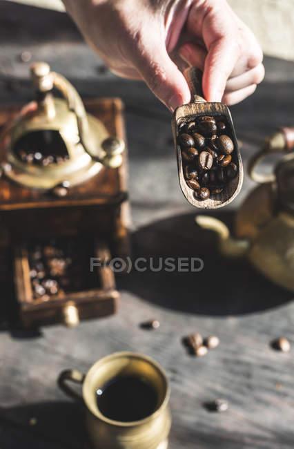 Frau steckt Kaffeebohnen in Mühle — Stockfoto