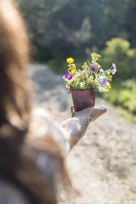 Mulher segurando vaso de flores — Fotografia de Stock