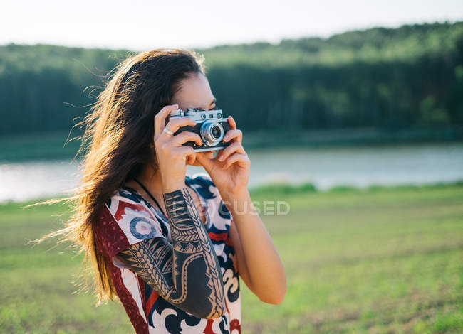 Woman with tattoo taking a photo — Stock Photo