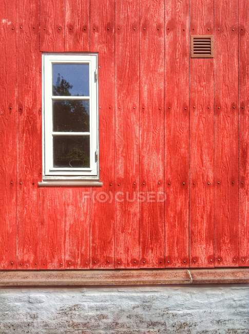 Exterior view of red wooden house with white window — Stockfoto