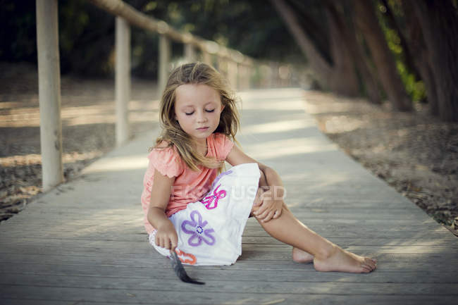 Girl sitting on a wooden boardwalk and playing with feather — Stock Photo