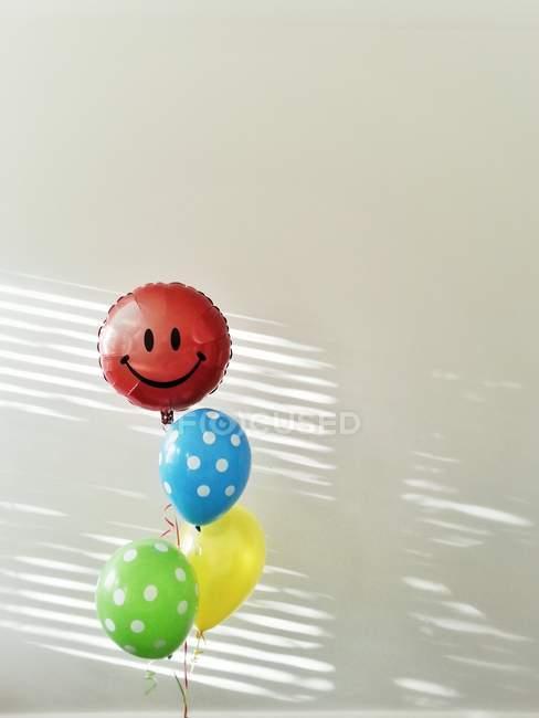 Quattro appesi in aria palloncini colorati con smiley sul rosso contro muro grigio — Foto stock