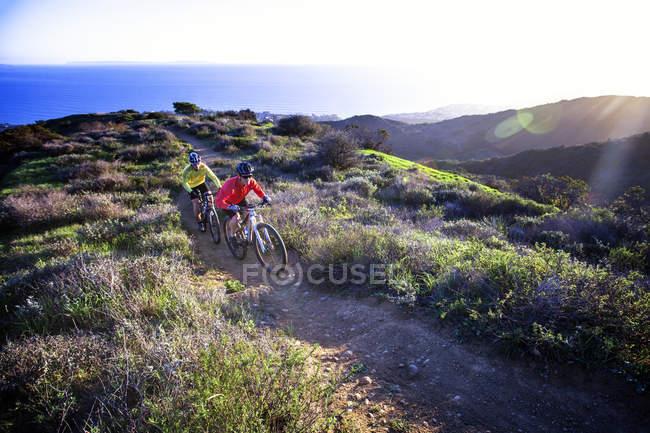 Two men mountain biking on coast — Stockfoto