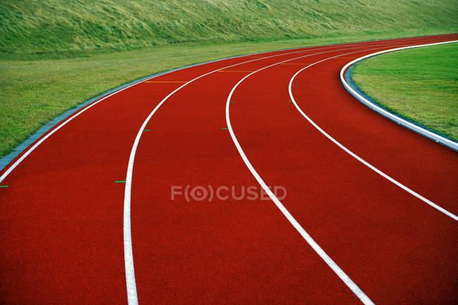 Крупный план яркой беговой дорожки и зеленой травы — стоковое фото