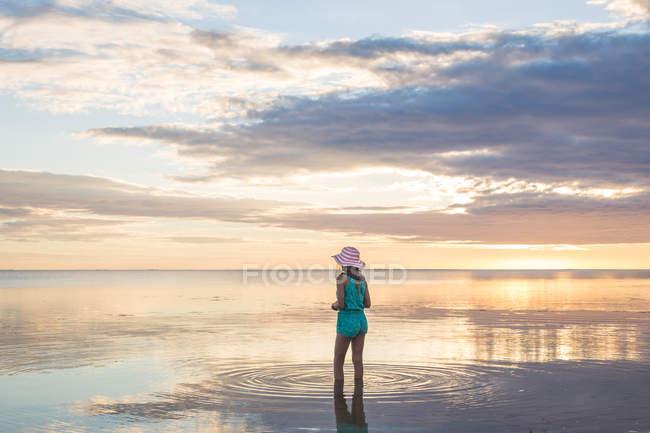Adolescente debout dans l'eau de mer et regardant le coucher du soleil — Photo de stock
