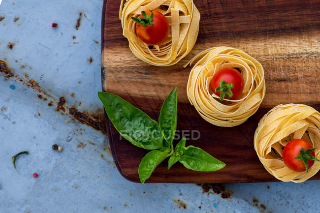 Food composition of fettuccini, tomatoes and basil on a chopping board, top view — Stock Photo